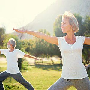 Elderly Couple outside doing yoga